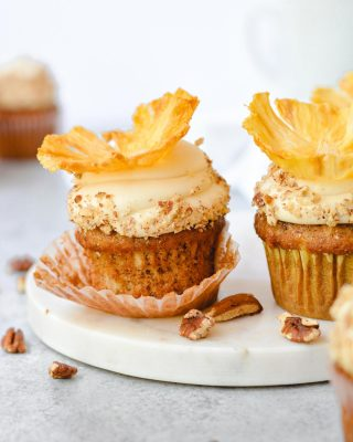 a couple of weeks ago in my stories i asked what y'all wanted to see next from my cookbook and these hummingbird cupcakes (from the book cover) won! they're topped with browned butter cream cheese frosting which is a new all time fave for me 🤤 plus dried pineapple flowers! (just as delicious without them, though!) recipe link in bio, friends! 💝